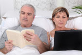 Man reading in bed while his wife surfs the internet — Stock Photo
