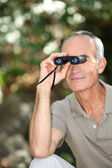 Senior man bird watching with binoculars — Stock Photo
