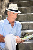 Old man reading magazine — Stock Photo
