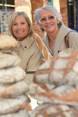 A 50 years old woman and a 70 years old woman in a bakery — Stock Photo