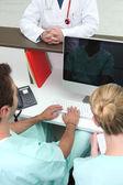 Medizinische assistentin sein spiegelbild auf einem computerbildschirm zu betrachten — Stockfoto