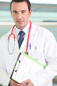 Male hospital doctor holding a clipboard — Stock Photo