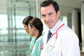Doctor standing with two nurses — Stock Photo