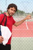 Giovane uomo all'esterno di un campo da tennis — Foto Stock