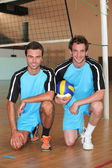 Team mates kneeling with volley ball on indoor court — Zdjęcie stockowe