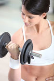 A woman lifting a barbell — Stock Photo