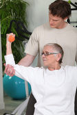 Coach helping senior lady to do exercises — Stock Photo