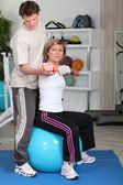 Donna matura lavorando con allenatore — Foto Stock