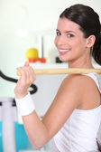 Girl in gym using wooden pole — Stock Photo
