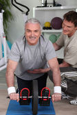Grey haired man with personal trainer — Stock Photo