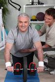 Homem de cabelo cinzento com personal trainer — Foto Stock