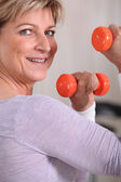 Mature woman using dumbbells — Stock Photo