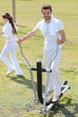 Man using an elliptical machine in an outdoor gym — Stock Photo