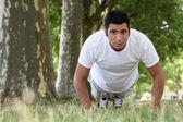 Svalnatý muž dělat kliky v parku — Stock fotografie
