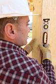 Builder med hjälp av ett vattenpass — Stockfoto