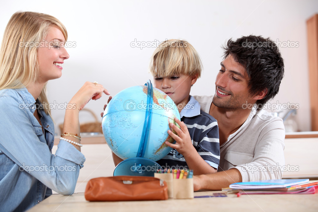 Little boy doing homework with his parents — Stock Photo #8340012