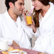 Young couple in bathrobe drinking orange juice out of straw — Stock Photo #8378874