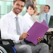 Man in wheelchair looking at notes — Stock Photo