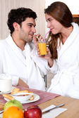 Young couple in bathrobe drinking orange juice out of straw — Stock Photo