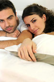 Attractive couple lying in bed — Stock Photo