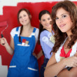 Trio of handygirls painting room red — Stock Photo
