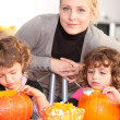 Stock Photo: Womhelping her children carve pumpkins