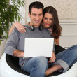 Young casual couple looking at a laptop — Stock Photo #8383359