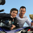 Boy winning a motorcycle racing cup - Stock Photo