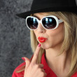 Pouting woman in sunglasses and hat — Stock Photo