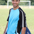 Smiling footballer with kitbag — Stock Photo