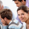 Smiling young woman with male colleagues out of focus in the background — Stock Photo #8385053
