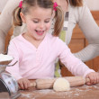 Little girl rolling out pastry — Stock Photo