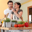 A woman feeding a carrot to her husband — Stock Photo