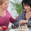 Two senior girlfriends playing chess — Stock Photo