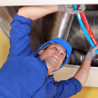 Worker holding blue and red pipes under air ducts — Stock Photo