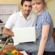 Couple cooking and using a laptop — Stock Photo #8385837