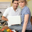 Couple cooking and using a laptop — Stock Photo