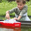 Schoolgirl playing with plastic boat — Stock Photo