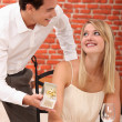 Couple in a restaurant with a gift — Stock Photo #8385990