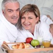 Middle-aged couple having breakfast in bed — Stock Photo #8387750