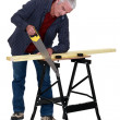 Carpenter sawing wood — Stock Photo #8387920
