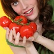 Portrait of red-haired girl posing with bunches of tomatoes — Stock Photo
