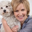 Smiling woman with small white dog — Stock Photo #8388342