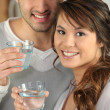 Couple drinking glasses of water — Stock Photo