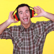 Happy man wearing earmuffs cancelling noise - Stock Photo