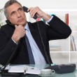 Stock Photo: Businessmanswering ringing telephones