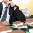 Pensive architect sat with model housing project — Stock Photo #8388749