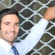 Smiling man standing in front of a shop grille - Stock Photo