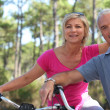 Older couple riding bikes in the countryside — Stock Photo #8389411