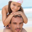 Little girl sitting on father's shoulders on the beach — Stock Photo #8389736
